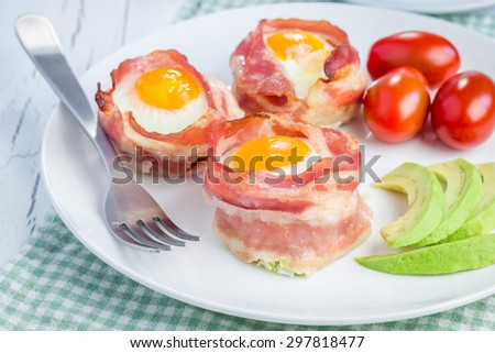 Baked eggs with avocado in bacon cups for breakfast  - stock photo