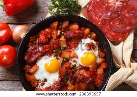 Baked eggs with chorizo and vegetables in the pan. close up top view  - stock photo