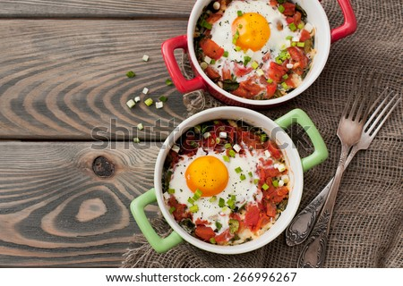 Baked eggs with tomatos and spinach on wooden background - stock photo