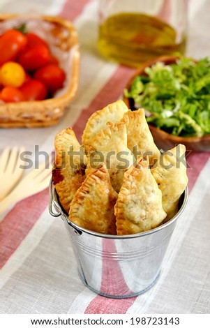 Baked empanadas with tomatoes and salad. Selective focus. Shallow depth of field - stock photo