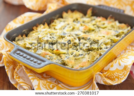 Baked farfalle pasta with spinach and artichoke - stock photo