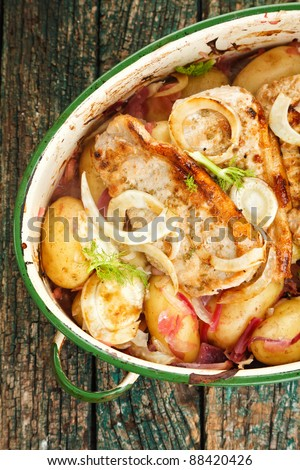 Baked fennel, pork, potatoes and red onions in an vintage enamel white cooking pot - stock photo