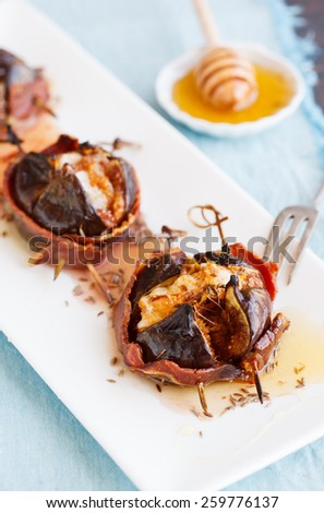 Baked figs with cheese wrapped in bacon.selective focus - stock photo