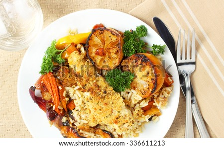Baked fish dinner served with golden roasted vegetables - stock photo