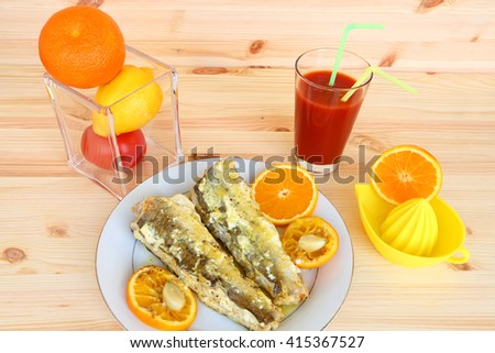 Baked fish ( Merluccius fish) with sour cream, olive oil and orange fruit with garlic and orange juice. Meal serving with tomato fresh on the wood. Mediterranean cuisine. - stock photo