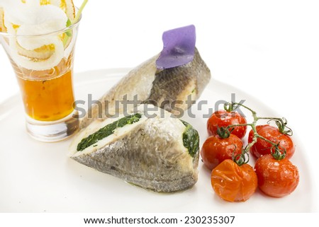 Baked fish on a white plate in a restaurant - stock photo