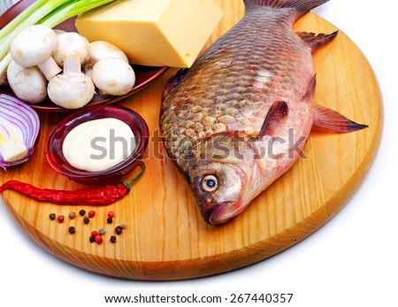 Baked fish with vegetables, sauce, red pepper on cutting board isolated on white - stock photo
