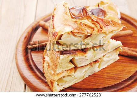 baked food : apple pie cuts on wooden plate over table with cinnamon sticks - stock photo