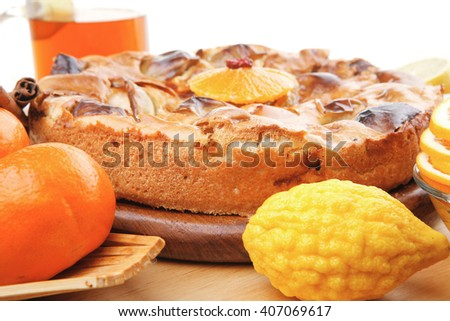 baked food : big apple pie served with fresh apples, raw lemon and mandarin,  tea cup on wooden plate over table - stock photo