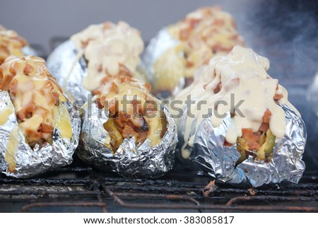 Baked Grilled Potato with stuffing cheese toping charcoal flame grill at farmer market stall  - stock photo
