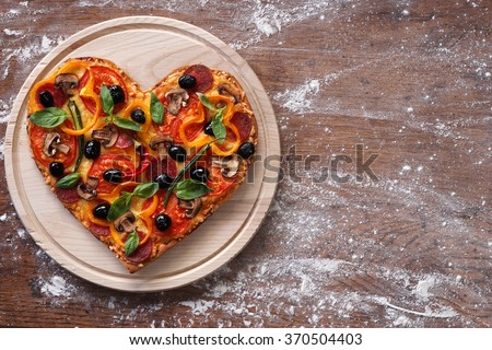Baked heart-shaped homemade pizza on a cutting board on rustic table, close-up. Happy Valentines day. love concept - stock photo