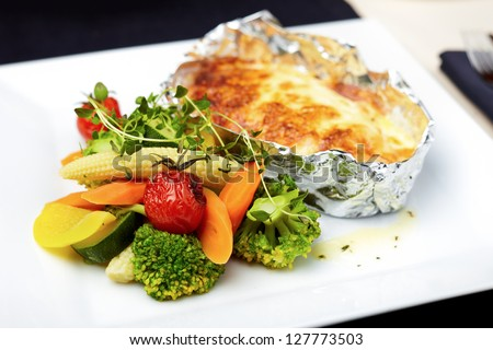 Baked in foil salmon with vegetables - stock photo