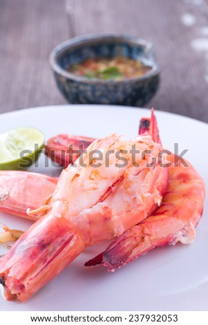 Baked king pranws with spicy sauce on wood table - stock photo