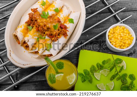 Baked meat tortilla with cheddar cheese, chilli peppers and corn, lime drink - stock photo