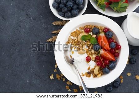 baked muesli with fresh berries and yogurt for breakfast, top view, horizontal - stock photo