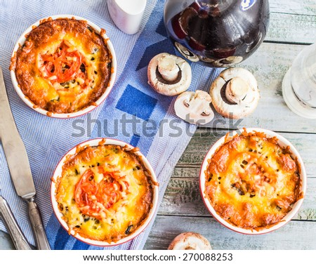 Baked mushroom julienne with tomato and cheese in red pots, top view, lunch on gray board - stock photo