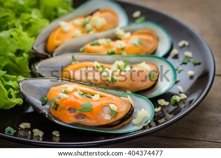 Baked mussels with garlic on plate - stock photo