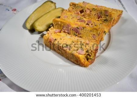 Baked or roasted egg pie or kind of quiche french style snack served on white plate with pickled cucumber. Made from eggs, smoked ham, parsley, pork meat and bread. Traditional food in Czech Republic. - stock photo