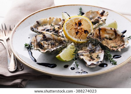 Baked oysters with sauce and cheese on a plate on a wooden background - stock photo