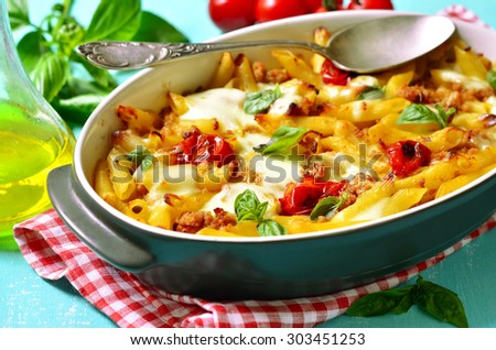 Baked pasta bolognese on a blue background. - stock photo