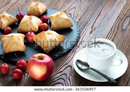 baked pies with apples on a black tray from slate, coffee in a white porcelain cup on a white saucer, tea spoon with patina,  paradise apples and red ripe apple with love heart on wooden table. - stock photo