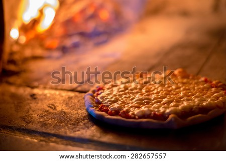 Baked pizza by the fire burn in  brick traditional vintage oven - stock photo