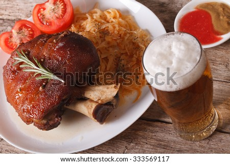 Baked pork shank and sauerkraut closeup on a plate and beer on the ...