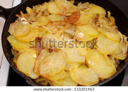 Baked potato and onion in the cast-iron frying pan - stock photo