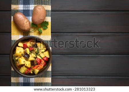 Baked potato, eggplant, zucchini and tomato casserole in rustic bowl, with raw potatoes and parsley leaf on kitchen towel, photographed overhead on dark wood with natural light - stock photo