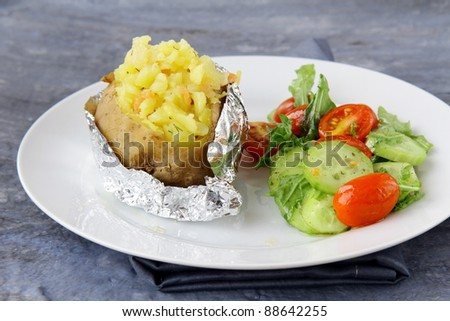 Baked potato filled with sour cream and  cheese, with salad - stock photo