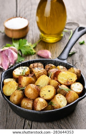 Baked potato in frying pan on rustic table - stock photo