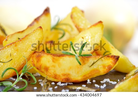 Baked potato wedges with rosemary served on a shabby cutting board with potatoes in the background - stock photo