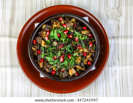 Baked potato with chicken meat served pomegranet and green herbs - stock photo