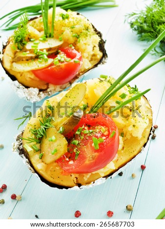Baked potato with pickles, tomatoes and fresh greens. Shallow dof. - stock photo