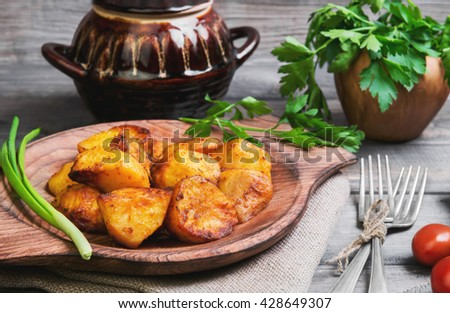 Baked potatoes roasted pieces, a ceramic pot saucepan of roasted pieces baked potatoes, rye bread, green onion, cherry tomatoes, silver fork, parsley, on a gray wooden rustic background - stock photo