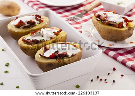 Baked potatoes stuffed with bacon and vegetables served with dill sauce - stock photo