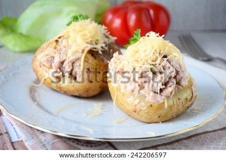 Baked potatoes stuffed with tuna salad and grated cheddar cheese - stock photo