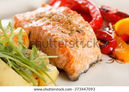 Baked prepared salmon fillet with vegetables, spices and arugula on a plate closeup - stock photo