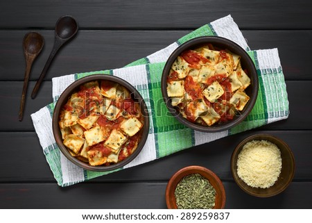 Baked ravioli with homemade tomato sauce in rustic bowls with grated cheese and dried oregano in small bowls, wooden spoons on the side, photographed overhead on dark wood with natural light - stock photo