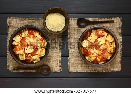 Baked ravioli with homemade tomato sauce in rustic bowls with grated cheese and wooden spoons on the side, photographed overhead on dark wood with natural light - stock photo