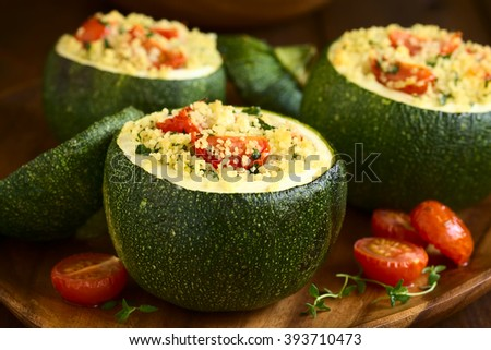 Baked round zucchini stuffed with couscous, cherry tomato and parsley served on wooden plate, photographed with natural light (Selective Focus, Focus on cherry tomato on the first stuffed zucchini) - stock photo