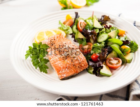 Baked Salmon Served with Tomatoes, Cucumbers, Avocado, Greens Salad - stock photo