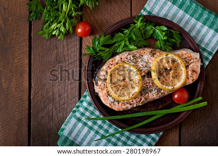 Baked salmon steak with lemon and herbs. Top view - stock photo