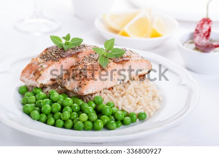 Baked salmon with rice, green peas and basil on a white ceramic plate on a white background - stock photo