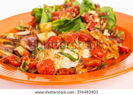 Baked salmon with roasted tomatoes and shallots on orange plate with potatoes and salad.  Shallow DOF and Selective focus on salmon. - stock photo
