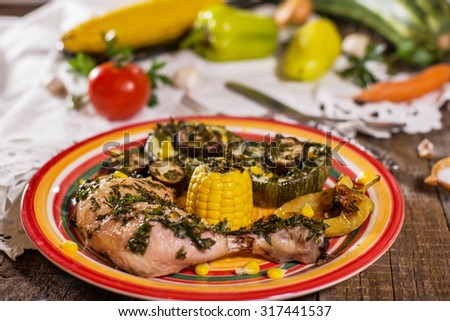 baked season vegetables in a colorful plate on rustic wooden table - stock photo