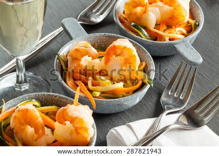 Baked shrimp with salad from carrot and zucchini in ceramic bowl with fork with glass of white wine with white napkin on the slate. grey background. closeup. horizontal - stock photo