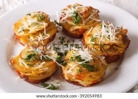 Baked sliced potatoes with cheese and dill close-up on a plate on the table. horizontal