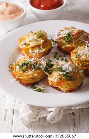 Baked sliced potatoes with Parmesan close-up on a plate on the table. Vertical