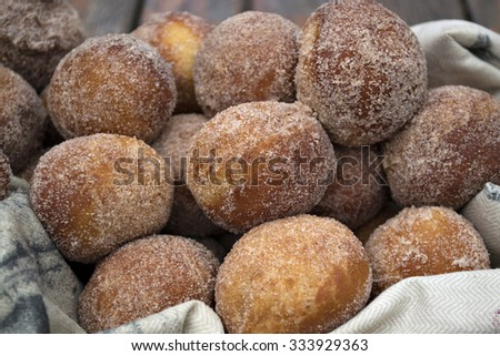 Baked snickerdoodle donut holes coated with sugar and cinnamon in a basket. - stock photo